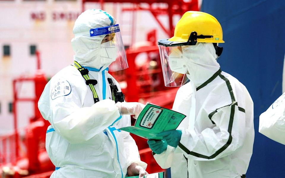 Police officers in protective gear explain Covid precautions at Nanjing port in China's eastern Jiangsu province - STR/AFP via Getty Images