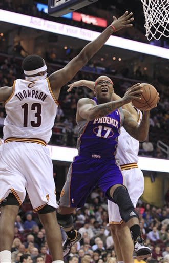 Phoenix Suns' P.J. Tucker (17) jumps to the basket between Cleveland Cavaliers' Tristan Thompson (13) and another defender during the second quarter of an NBA basketball game Tuesday, Nov. 27, 2012, in Cleveland. (AP Photo/Tony Dejak)