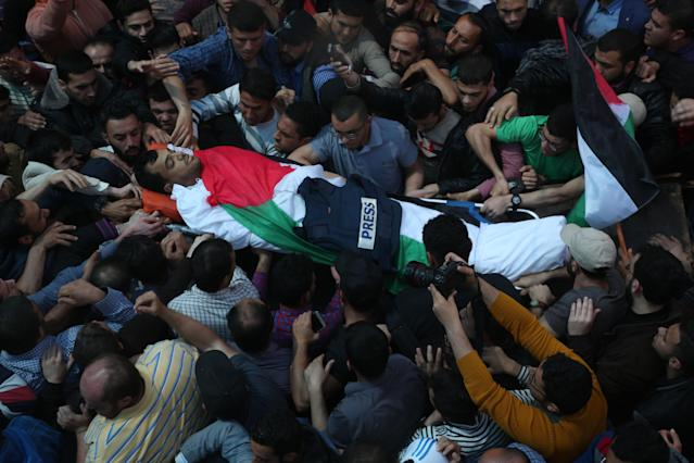 <p>Mourners and journalists carry the body of Palestinian journalist Yasser Murtaja, during his funeral in Gaza City on April 7, 2018. Among those killed at Friday's protest was Yasser Murtaja, a photographer with the Gaza-based Ain Media agency, who died from his wounds after being shot, the local health ministry said. Murtaja's company confirmed his death, with witnesses saying he was close to the front of the protests in Southern Gaza when he was hit. (Photo: Majdi Fathi/NurPhoto via Getty Images) </p>