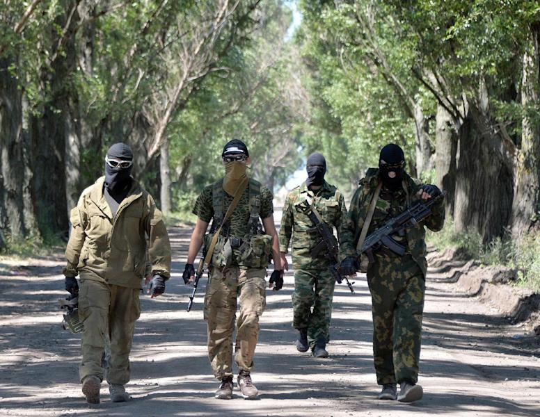 Former militants of the so-called People's Republic of Donetsk sided with the Ukrainian army, patrol near a check-point in the north of the Donetsk region on July 3, 2014 (AFP Photo/Genya Savilov)