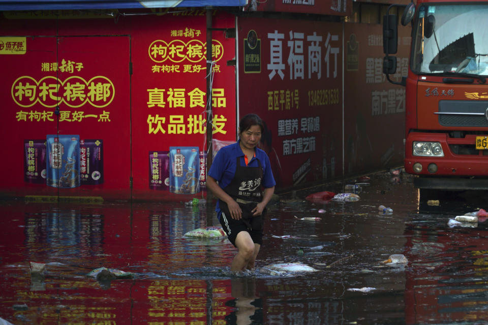 Xing, a shop owner at Yubei Agricultural and Aquatic Products World, walks in floodwaters at the market in Xinxiang in central China's Henan Province, Monday, July 26, 2021. Record rain in Xinxiang last week left the produce and seafood market soaked in water. Dozens of people died in the floods that immersed large swaths of central China's Henan province in water. (AP Photo/Dake Kang)