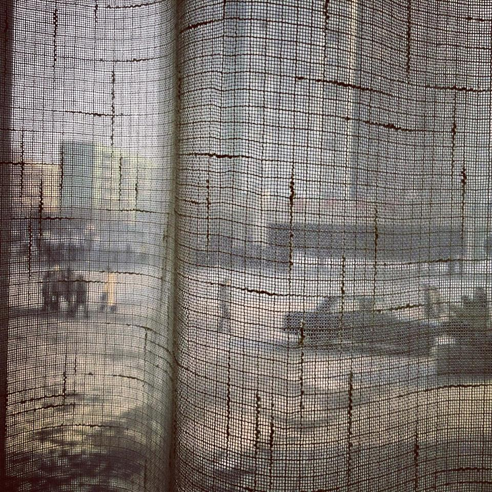 In this Jan. 8, 2013 photo taken with an iPod Touch and posted to instagram on Jan. 8, 2013, North Koreans walk along a Pyongyang street and seen through a coffee shop window curtain. On Jan. 18, 2013, foreigners were allowed for the first time to bring mobile phones into North Korea. And this week the local service provider, Koryolink, is allowing foreigners to access the Internet on a data capable 3G connection on mobile phones. (AP Photo/David Guttenfelder)