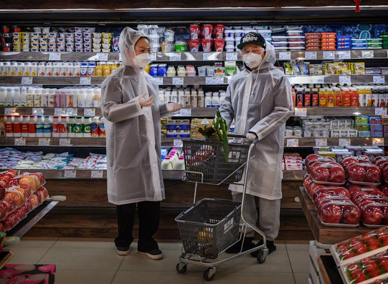 A Chinese couple wearing plastic coats and protective masks shop for groceries at a Beijing supermarket.