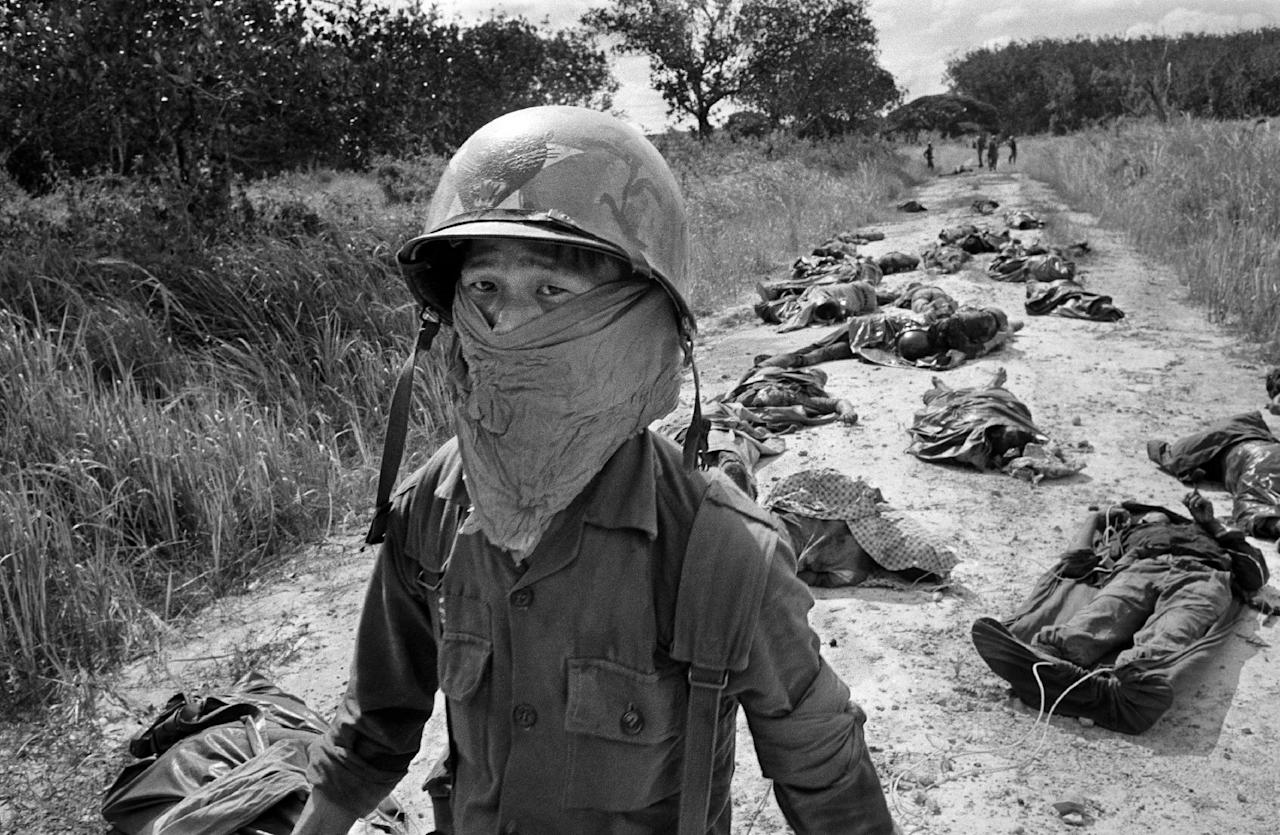FILE - In this Nov. 27, 1965 file photo taken by Associated Press photographer Horst Faas, a Vietnamese litter bearer wears a face mask to keep out the smell as he passes the bodies of U.S. and Vietnamese soildiers killed in fighting against the Viet Cong at the Michelin rubber plantation, about 45 miles northeast of Saigon. Faas, a prize-winning combat photographer who carved out new standards for covering war with a camera and became one of the world's legendary photojournalists in nearly half a century with The Associated Press, died Thursday May 10, 2012. He was 79. (AP Photo/Horst Faas, File)