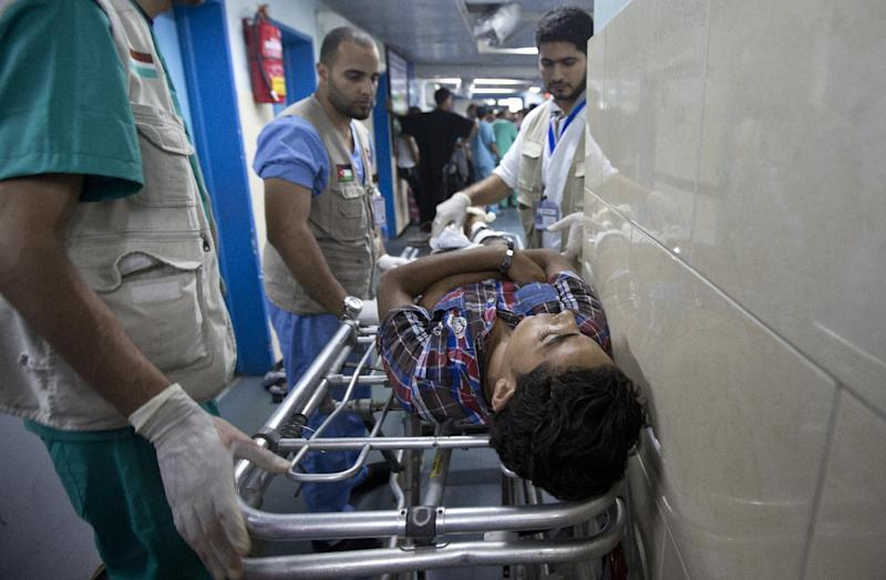 A wounded Palestinian man receives medical treatment in the corridor of the al-Shifa hospital after an Israeli air strike on Gaza City on August 22, 2014 (AFP Photo/Mahmud Hams)