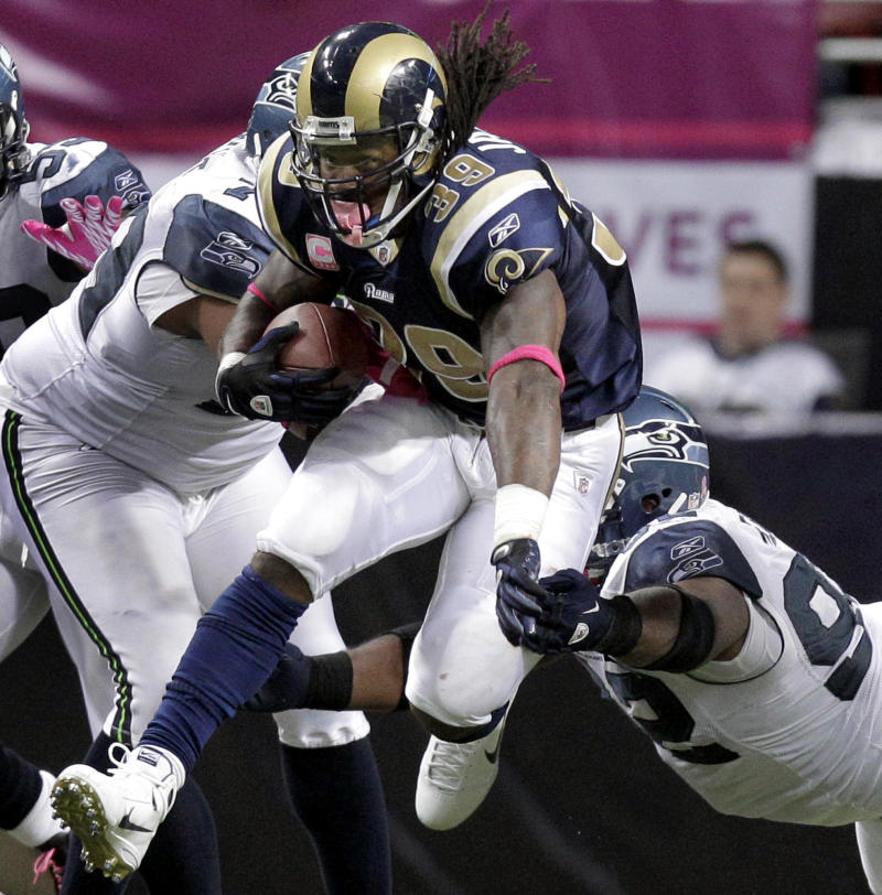 St. Louis Rams running back Steven Jackson, left, leaps past Seattle Seahawks defensive tackle Brandon Mebane, right, on his way to a 15-yard gain during the fourth quarter of an NFL football game Sunday, Oct. 3, 2010, in St. Louis. The gain made Jackson the Rams' second all-time leading rusher behind Eric Dickerson and helped give his team a 20-3 victory. (AP Photo/Jeff Roberson)