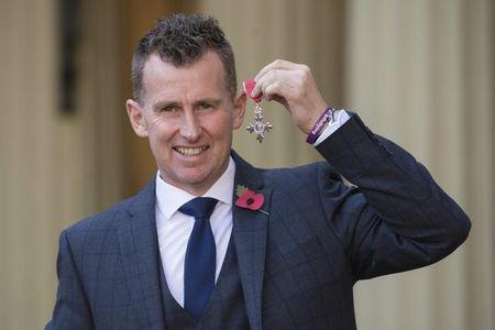 Rugby referee Nigel Owens poses with his MBE which he received  from the Duke of Cambridge at Buckingham Palace in London, Britain November 11, 2016. REUTERS/Stefan Rousseau/Pool