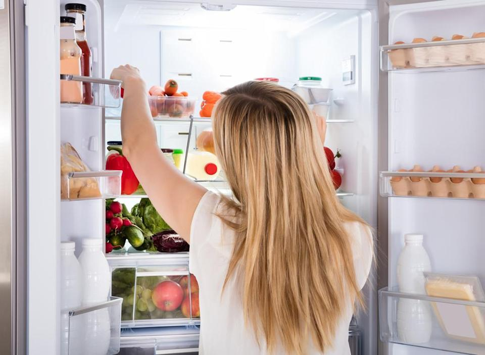 Hungry woman looking for food in the refrigerator