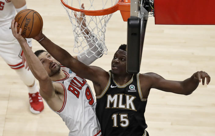 Chicago Bulls' Nikola Vucevic, left, and Atlanta Hawks' Clint Capela (15) vie for a rebound during the first half of an NBA basketball game Friday, April 9, 2021, in Atlanta. (AP Photo/Ben Margot)