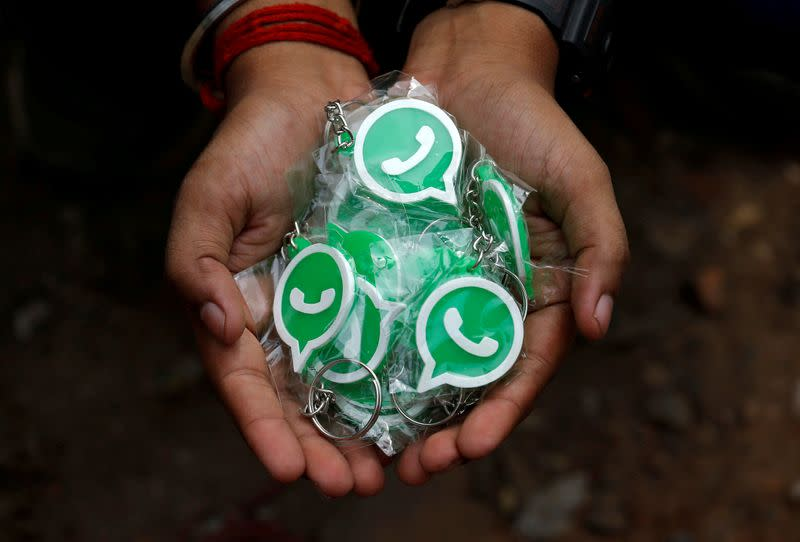 FILE PHOTO: A WhatsApp-Reliance Jio representative displays key chains with the logo of WhatsApp for distribution during a drive by the two companies to educate users, on the outskirts of Kolkata