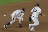 A ball scoots past New York Yankees second baseman DJ LeMahieu (26) as shortstop Gleyber Torres (25) overruns it, during the seventh inning of a baseball game, Tuesday, Aug. 11, 2020, in New York. The Braves' Austin Riley scored on the play, and LeMahieu was charged with an error on the play. (AP Photo/Kathy Willens)