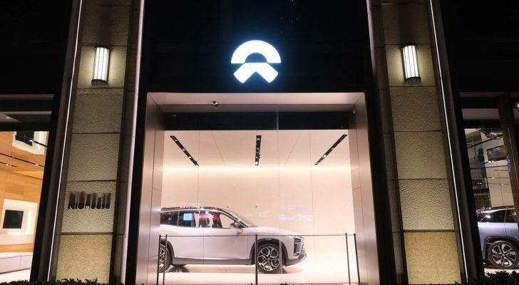 NIO stock: A shot from the outside of a Nio display room at night.