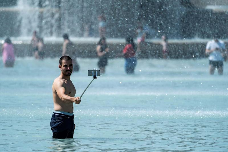 A man takes a selfie picture with a mobile-phone as he stands in the middle of the Trocadero fountain in Paris. (AFP/Getty Images)