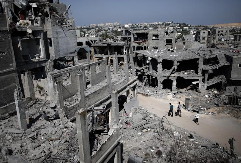 Palestinians walk past destroyed buildings in the northern Gaza Strip city of Beit Hanun on August 22, 2014 (AFP Photo/Thomas Coex)