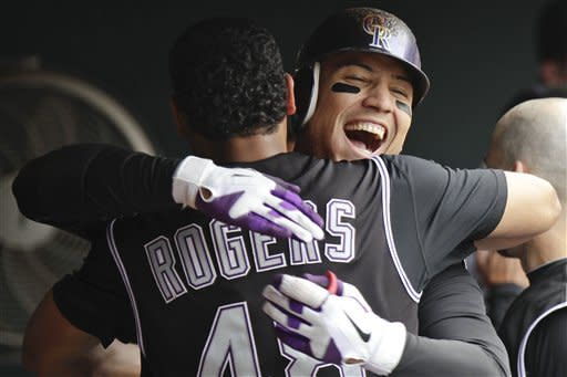 Colorado Rockies' Carlos Gonzalez, right, hugs Esmil Rogers after hitting a two-run home run against the Los Angeles Dodgers during the eighth inning of a baseball game Wednesday, May 2, 2012, in Denver. The Rockies won 8-5. (AP Photo/Barry Gutierrez)