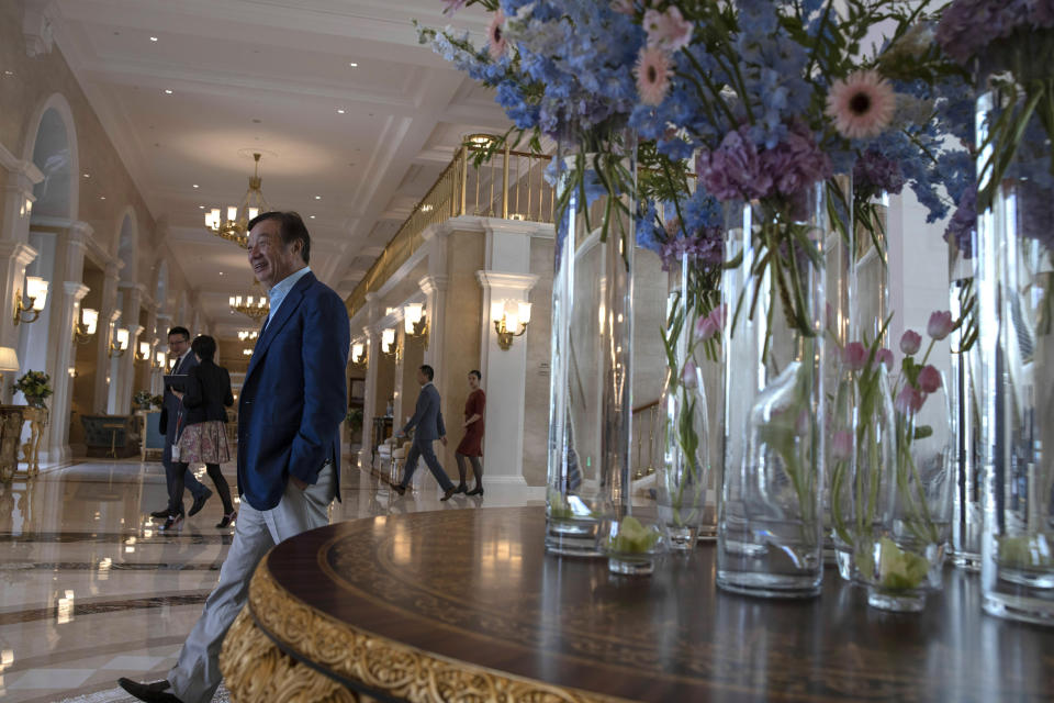 In this Aug. 20, 2019, photo, Huawei's founder Ren Zhengfei, walks past an opulent corridor in the company campus in Shenzhen in Southern China's Guangdong province. Ren says its troubles with President Donald Trump are hardly the biggest crisis he has faced while working his way from rural poverty to the helm of China's first global tech brand. (AP Photo/Ng Han Guan)
