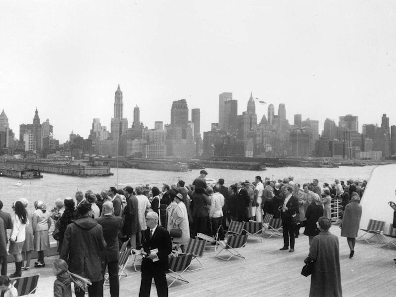 Passengers on the QE2 line the rails as the ship arrives in New York in 1969 (Getty)