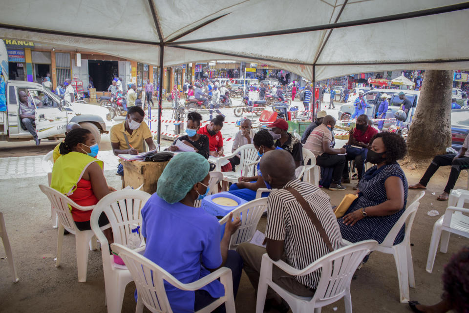 People wait to receive coronavirus vaccinations at a streetside vaccination tent in downtown Kampala, Uganda Tuesday, Sept. 7, 2021. Uganda is accelerating its vaccination drive in order to administer 128,000 doses that recently arrived and expire at the end of September. (AP Photo/Nicholas Bamulanzeki)