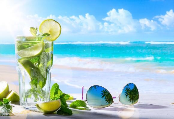 A cocktail drink with fresh lime and mint leaves next to sunglasses on a table, with a beach in the background.