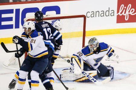 Apr 10, 2019; Winnipeg, Manitoba, CAN; St. Louis Blues goalie Jordan Binnington (50) makes a save in front of Winnipeg Jets forward Kevin Hayes (12) during the second period in game one of the first round of the 2019 Stanley Cup Playoffs at Bell MTS Place. Mandatory Credit: Terrence Lee-USA TODAY Sports