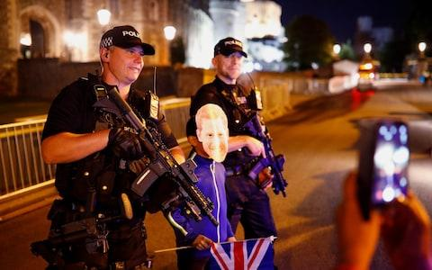 Armed police pose with a boy in a Prince Harry mask for a photo - Credit: Reuters