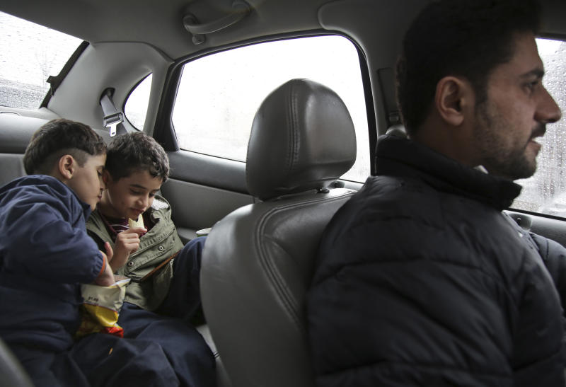 In this Thursday, March 21, 2019, photo, brothers Adel Ahmed, 9, center, and Mutaz Ahmed, 7, video chat with their mother in Yemen while their father Sadek Ahmed drives them to a doctor's appointment in the Brooklyn borough of New York. Their mother, Amena Abdulkarem, is stuck in Yemen with her two younger sons, the boys' brothers. In hourslong weekend calls with their mother, the children always have the same question: When are you going to come to America? (AP Photo/Seth Wenig)