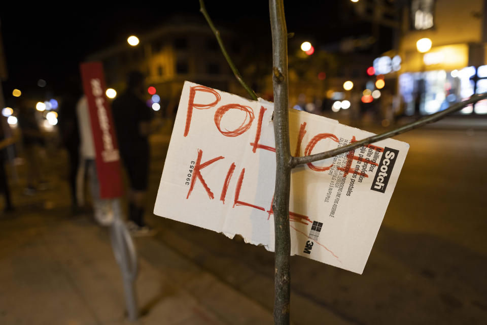 An anti-police sign hangs on a tree after a vigil held for Winston Boogie Smith Jr. early on Saturday, June 5, 2021. Authorities say Smith, wanted on a weapons violation, fired a gun from inside his vehicle before he was fatally shot by members of a federal task force as they were trying to arrest him. (AP Photo/Christian Monterrosa)