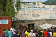 Civilians stand outside the Kangbayi central prison in Beni