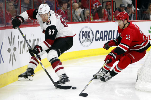 Arizona Coyotes' Lawson Crouse (67) battles behind the net with Carolina Hurricanes' Brett Pesce (22) during the second period of an NHL hockey game, Sunday, Dec. 16, 2018, in Raleigh, N.C. (AP Photo/Karl B DeBlaker)