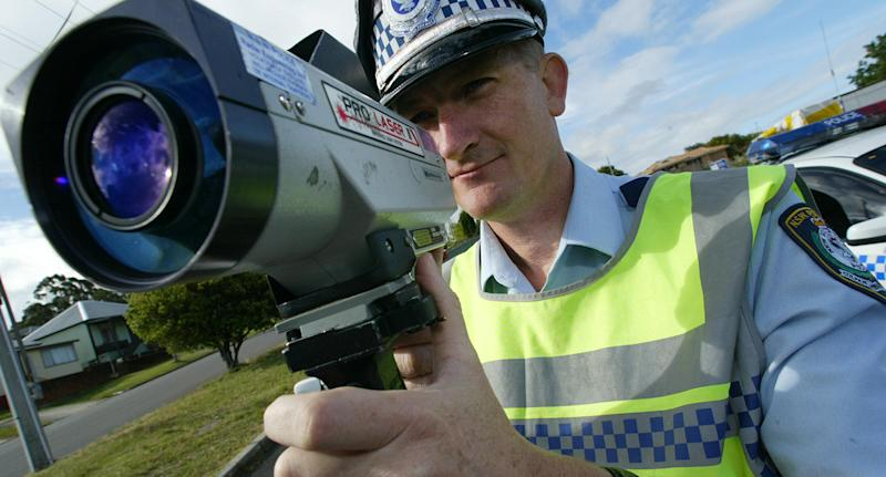 Tuggerah Lakes highway patrol supervisor Gary Carr stands with a speed camera.