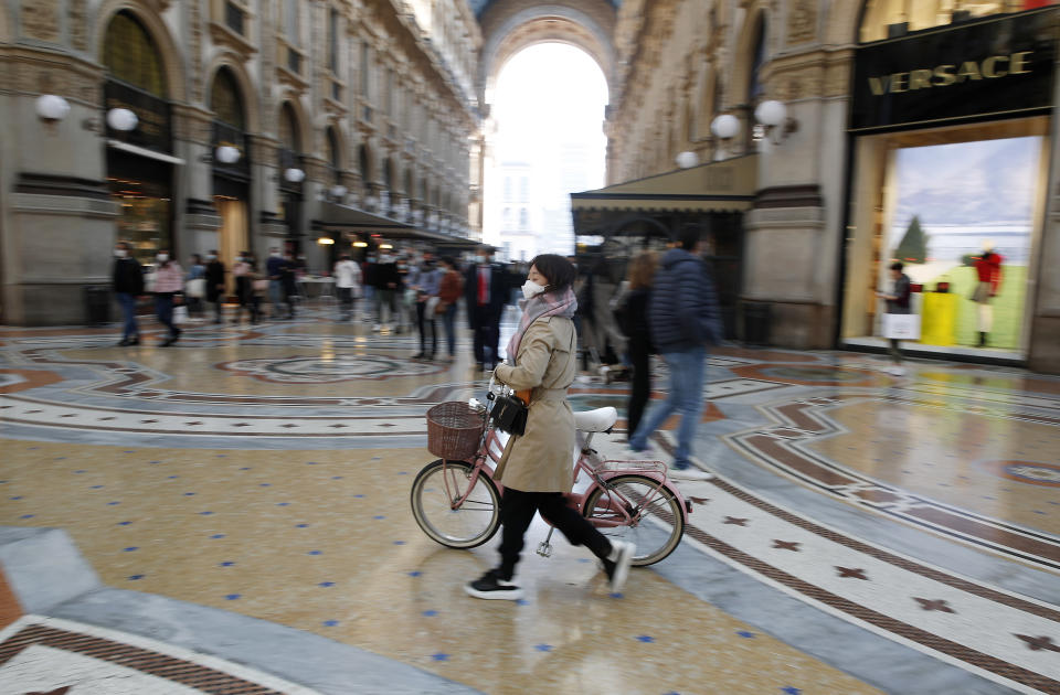 A woman wearing a sanitary mask walks in downtown Milan, Italy, Saturday, Oct. 17, 2020. Italy's northern Lombardy region, where the European outbreak began in late February, has taken new measures to contain rebounding coronavirus infections, limiting bar service and alcohol sales, banning contact sports and closing bingo parlors. (AP Photo/Antonio Calanni)