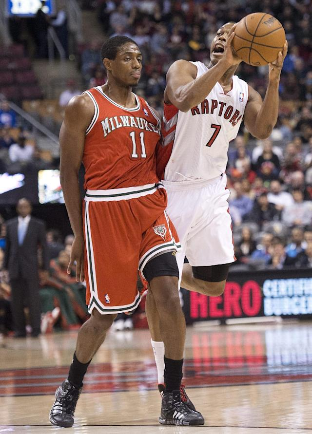 Toronto Raptors guard Kyle Lowry (7) looks to pass against Milwaukee Bucks guard Brandon Knight, left, during first half NBA basketball game in Toronto, Monday, Jan. 13, 2014. (AP Photo/The Canadian Press, Nathan Denette)