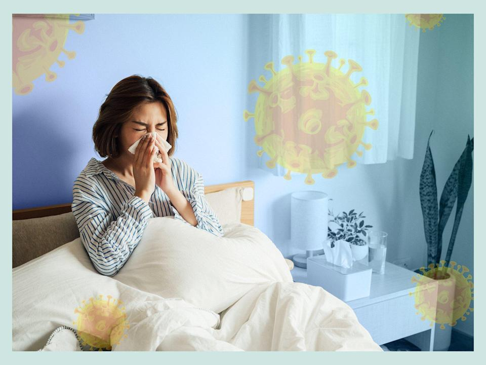 Sick woman sitting in bed with COVID-19 cells floating around her