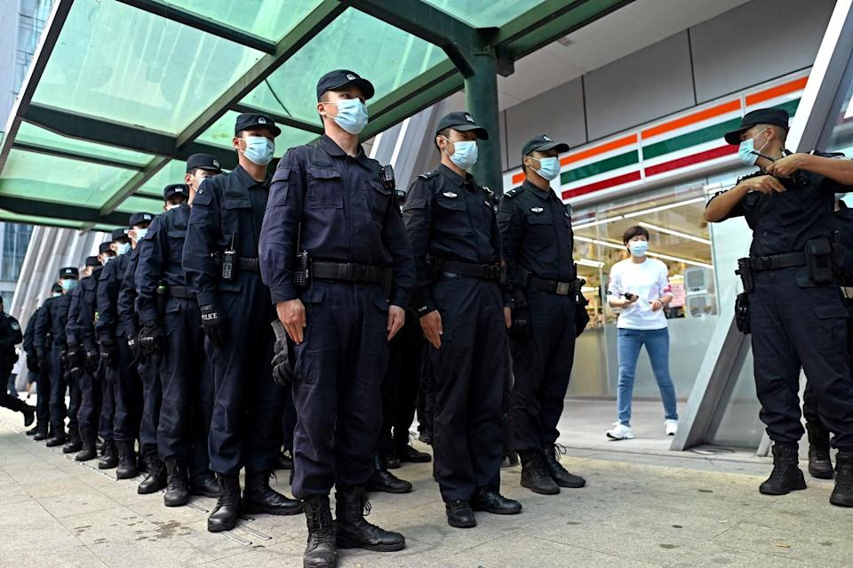 Policemen stand in formation at the Evergrande headquarters