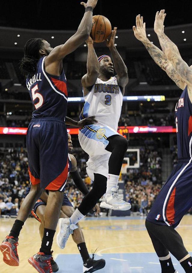 Denver Nuggets guard Ty Lawson (3) goes up for a shot against Atlanta Hawks' DeMarre Carroll (5) and Pero Antic during the third quarter of an NBA basketball game Thursday, Nov. 7, 2013, in Denver. (AP Photo/Jack Dempsey)