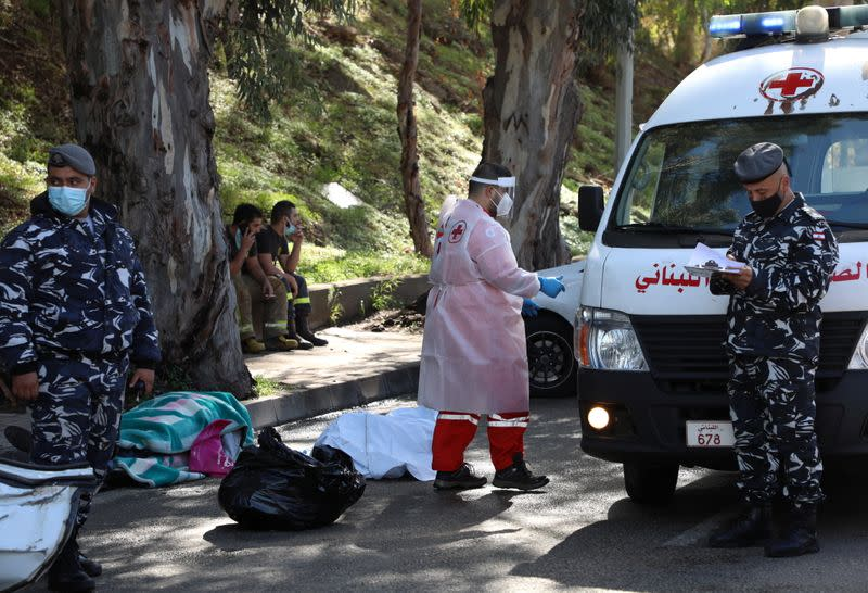 Members of the Lebanese police stand next to a dead body in Hadath