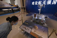 A visitor to an exhibition on China's space program looks at a life size model of the Chinese Mars rover Zhurong, named after the Chinese god of fire, at the National Museum in Beijing on Thursday, May 6, 2021. China has landed a spacecraft on Mars for the first time in the latest advance for its space program. The official Xinhua News Agency said Saturday, May 15, that the lander had touched down, citing the China National Space Administration. Chinese characters read: Build a Space Power. (AP Photo/Ng Han Guan)