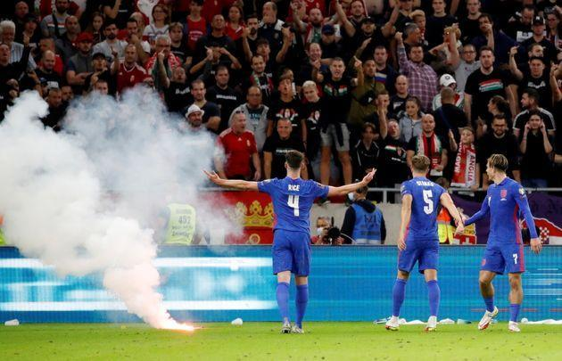 Declan Rice, John Stones and Jack Grealish react after a flare is thrown on to the pitch by Hungary fans after Harry Maguire scored their third goal. (Photo: Leonhard Foeger via Reuters)