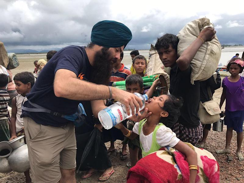 A volunteer gives water to a child said to be fleeing violence in Burma: Khalsa Aid