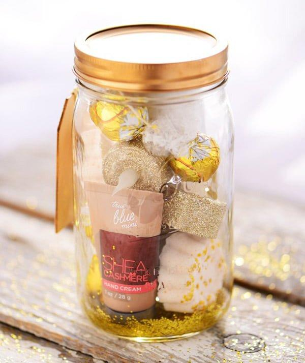 """<p>This <a href=""""https://www.thegunnysack.com/golden-pampering-mason-jar-gift/"""" target=""""_blank"""">golden pampering mason jar</a> present from The Gunny Sack is ideal for the ultimate indulgence package. With bath bombs, a foot soak, sugar scrub, chocolates and more, this kit promotes blissful relaxation.</p>"""