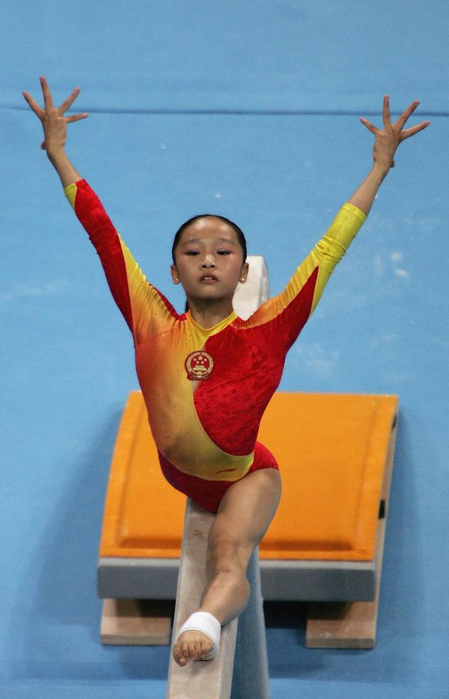 ATHENS - AUGUST 23: Li Ya of China poses poses during her performance in the women's artistic gymnastics balance beam finals on August 23, 2004 during the Athens 2004 Summer Olympic Games at the Olympic Sports Complex Indoor Hall in Athens, Greece. (Photo by Clive Brunskill/Getty Images)
