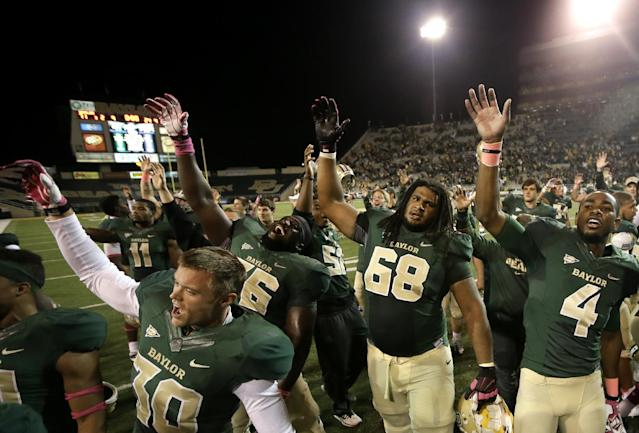 Baylor's Cody Wetsel, front left, Jason Osei, Cyril Richardson (68) and Jay Lee (4) celebrate on the field following an NCAA college football game against Iowa State, Saturday, Oct. 19, 2013, in Waco, Texas. Baylor won 71-7. (AP Photo/Tony Gutierrez)