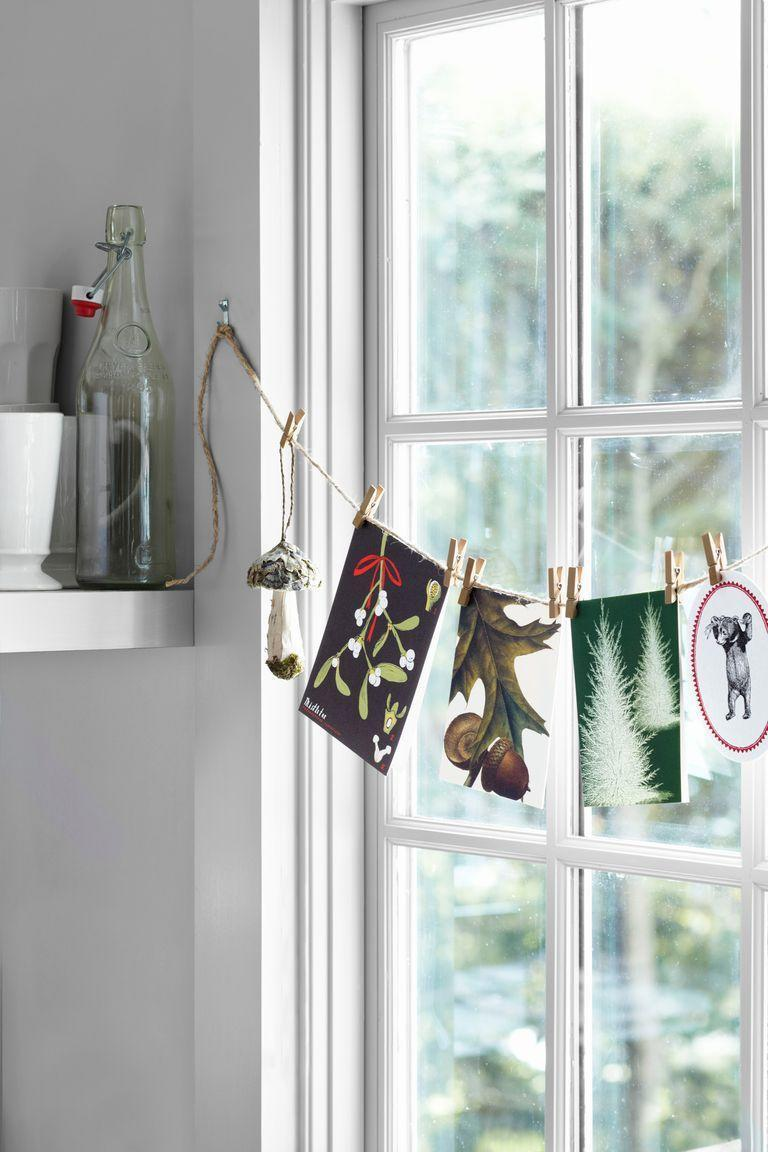"""<p>Create a garland out of this season's greetings, and string across your window.</p><p><a class=""""link rapid-noclick-resp"""" href=""""https://www.amazon.com/BAZIC-Mini-Natural-Clothespins-Wood/dp/B003BXE6ZI/?tag=syn-yahoo-20&ascsubtag=%5Bartid%7C10050.g.23343056%5Bsrc%7Cyahoo-us"""" rel=""""nofollow noopener"""" target=""""_blank"""" data-ylk=""""slk:SHOP MINI CLOTHESPINS"""">SHOP MINI CLOTHESPINS</a> </p>"""