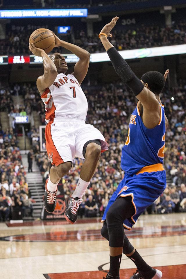 Toronto Raptors' Kyle Lowry, left, shoots against New York Knicks' Toure' Murry during first-half NBA basketball game action in Toronto, Saturday, Dec. 28, 2013. (AP Photo/The Canadian Press, Chris Young)