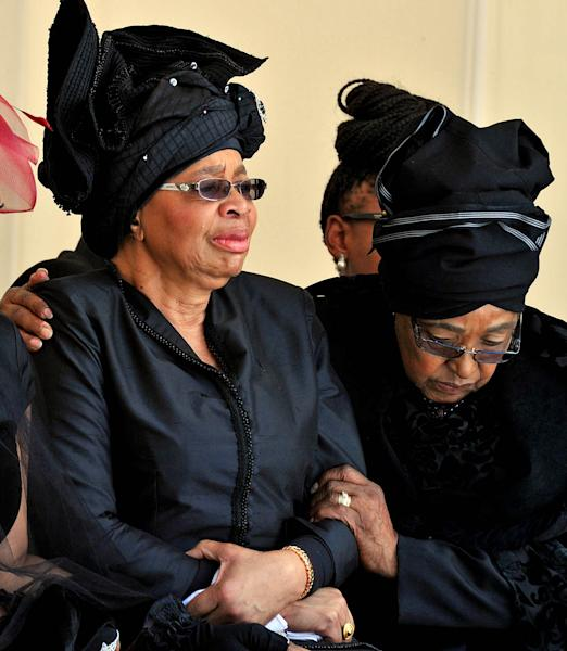 Nelson Mandela's widow Graca Machel, and Winnie Madikizela-Mandela, Nelson Mandela's former wife, watch as former South African President Nelson Mandela's casket arrives at his burial site following his funeral service in Qunu, South Africa, Sunday, Dec. 15, 2013. (AP Photo/Elmond Jiyane, GCIS)