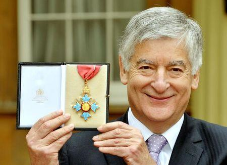 Former FA chairman David Bernstein  poses with his CBE medal after being knighted by Britain's Prince Charles at Buckingham Palace in London