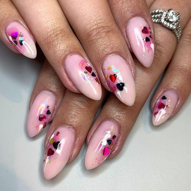 """<p>Grab a bunch of small, heart-shaped glitter and place them across a pale pink nail for a classic Valentine's Day nail look. </p><p><a href=""""https://www.instagram.com/p/B8VOgwhlmxY/"""" rel=""""nofollow noopener"""" target=""""_blank"""" data-ylk=""""slk:See the original post on Instagram"""" class=""""link rapid-noclick-resp"""">See the original post on Instagram</a></p>"""