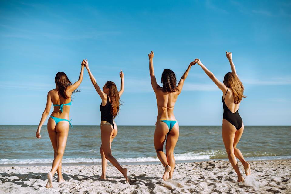 Four young girls run to swim in the sea. Summer holidays, vacation, relax and lifestyle concept.