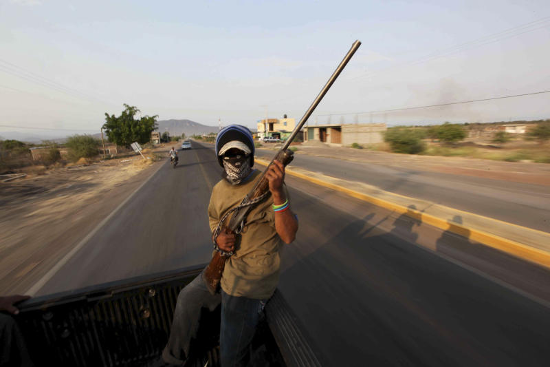 In this May 20, 2013 photo, an armed man belonging to a local self-defense group patrols from the back of a pick-up truck in the town of Buenavista, Mexico. Self-defense groups started to spring up in February to fight back the Knights Templar drug cartel which is extorting protection payments from cattlemen and lime growers, butchers and even marijuana growers. The federal government sees both the self-defense forces and the cartel as dangerous enemies. (AP Photo/Marco Ugarte)