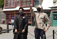 A guest wearing a facemask holds a wand in the Harry Potter themed section on the opening day for season and annual pass holders of Universal Studios Hollywood